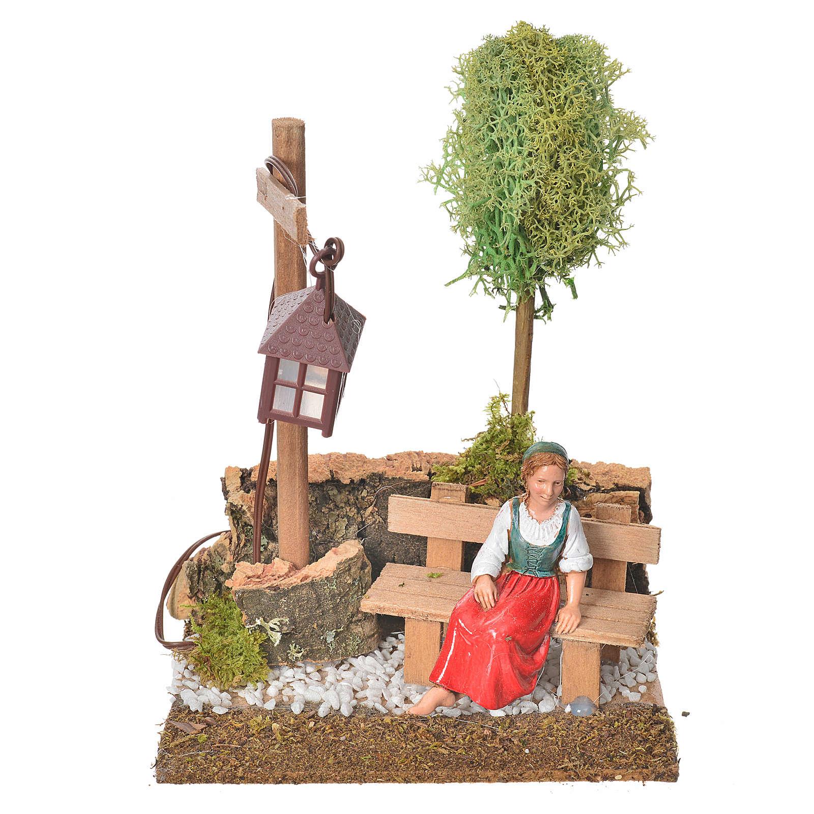 Mujer sentada en un banco con farol escenografía belén 3