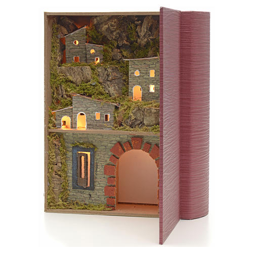 Illuminated village with grotto for nativities inside a book 24x 2