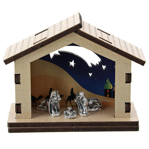Nativity in metal with wood shack and printed desert in the background 5 cm 1
