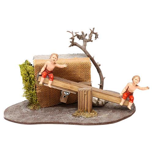 Bambini Oliver su altalena con movimento per presepi di 10 cm 1