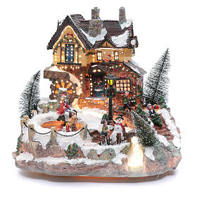 Winter village with ice skating rink, movement and lights 25x30x30 cm s1