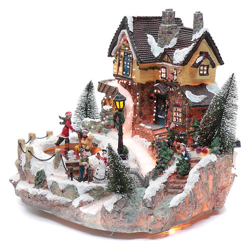 Winter village with ice skating rink, movement and lights 25x30x30 cm 2