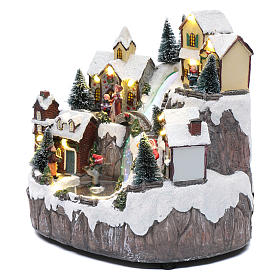 Villaggio di Natale con ruscello di fibra e musica 25x25x17 cm s2
