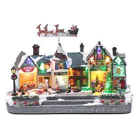 Bożonarodzeniowe miasteczko oświetlone z melodią ruchem reniferów choinki postaci na zlodowaciałym jeziorze 27x41x17 cm s1