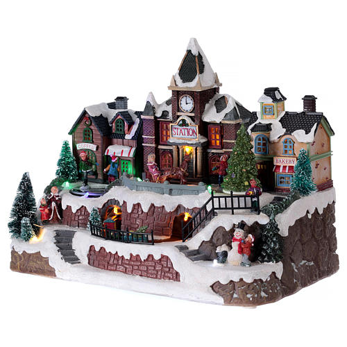 Animated musical Christmas village with train and iced lake