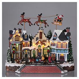 Cenário de Natal Pai Natal renas movimento 30x35x20 cm luzes música corrente s2