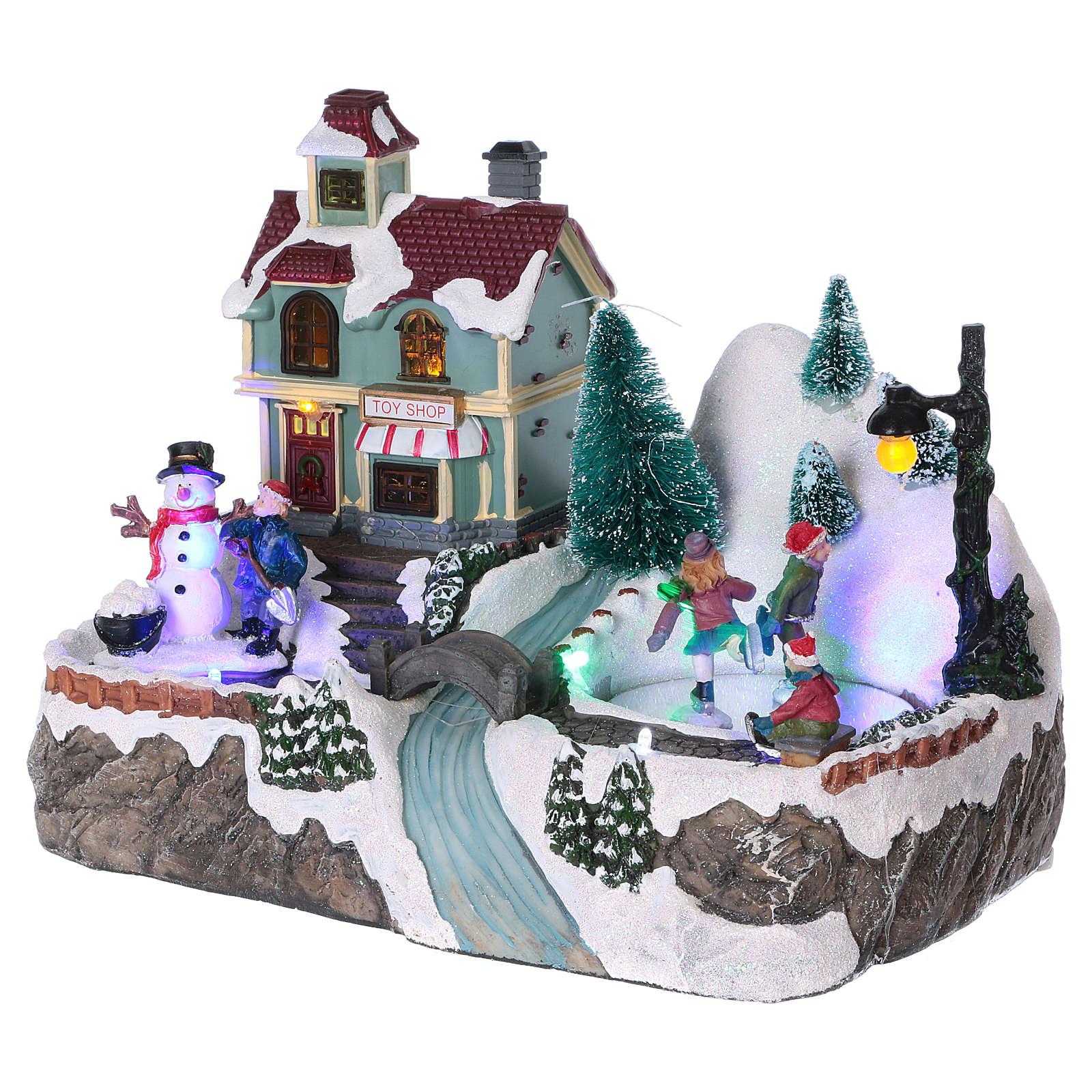 Dekoracja scenka świąteczna podświetlana ruchomi łyżwiarze sklep z zabawkami 20x25x16 cm na baterie zasilacz 3