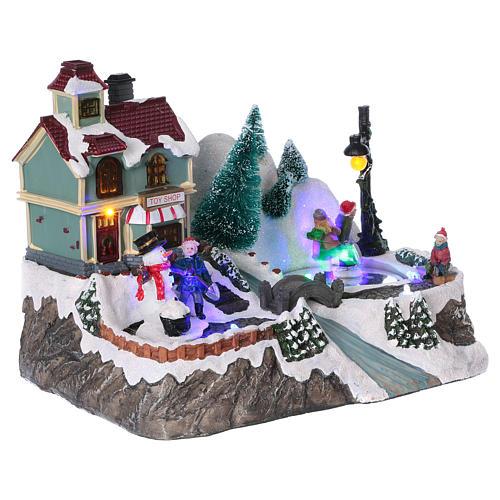 Dekoracja scenka świąteczna podświetlana ruchomi łyżwiarze sklep z zabawkami 20x25x16 cm na baterie zasilacz 4