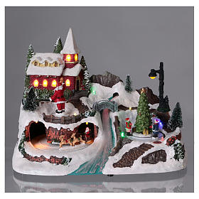 Christmas village with moving ice-skaters and Santa Claus 20x30x20 cm s2