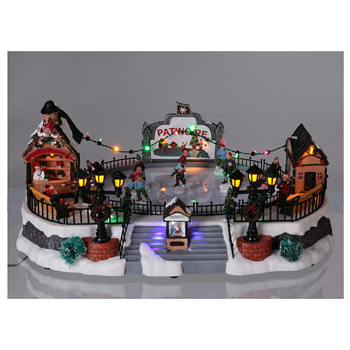 Christmas village with moving ice-skaters and gnome 20x40x25 cm 2