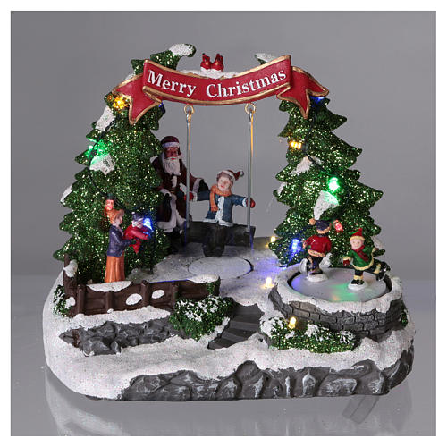 Christmas village with LED lights, moving ice-skaters and swing 20x25x20 cm 2