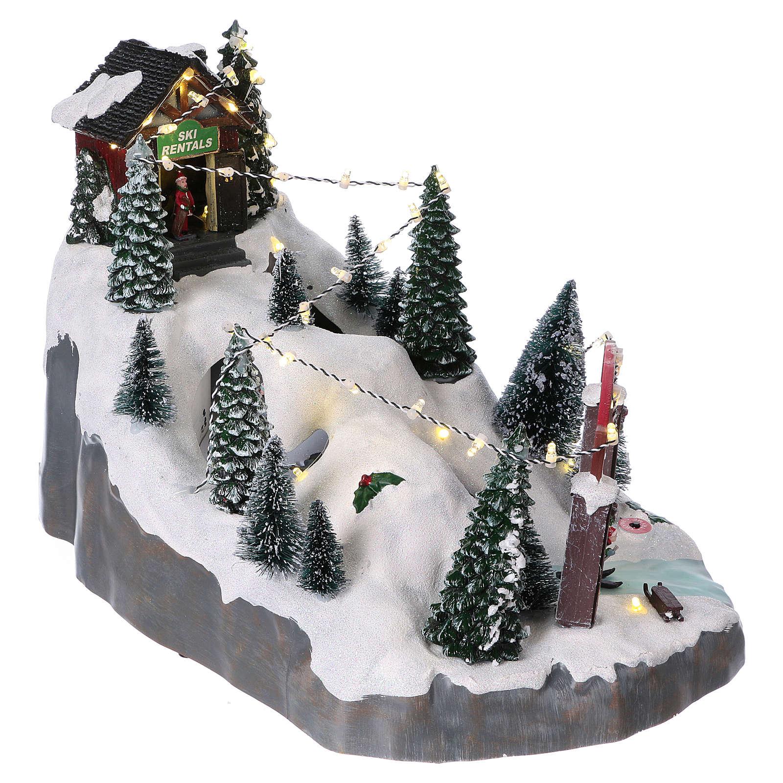 Villaggio natalizio 25x25x35 cm con sciatori movimento batteria e corrente 3