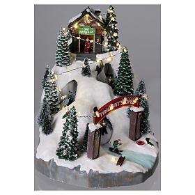 Villaggio natalizio 25x25x35 cm con sciatori movimento batteria e corrente s2
