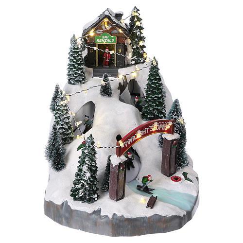 Villaggio natalizio 25x25x35 cm con sciatori movimento batteria e corrente 1