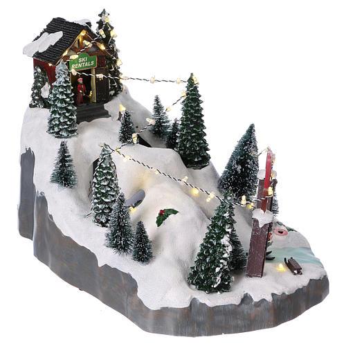 Villaggio natalizio 25x25x35 cm con sciatori movimento batteria e corrente 4
