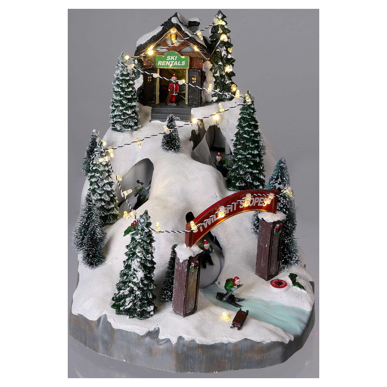 Miasteczko bożonarodzeniowe 25x25x35 cm z narciarzami ruchomymi na baterie i zasilacz 3