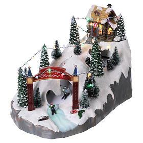 Villaggio natalizio 25x25x35 cm con sciatori movimento batteria e corrente s3