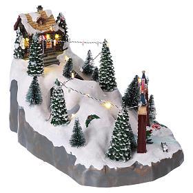 Villaggio natalizio 25x25x35 cm con sciatori movimento batteria e corrente s4