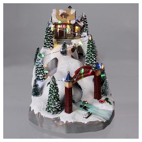 Villaggio natalizio 25x25x35 cm con sciatori movimento batteria e corrente 2