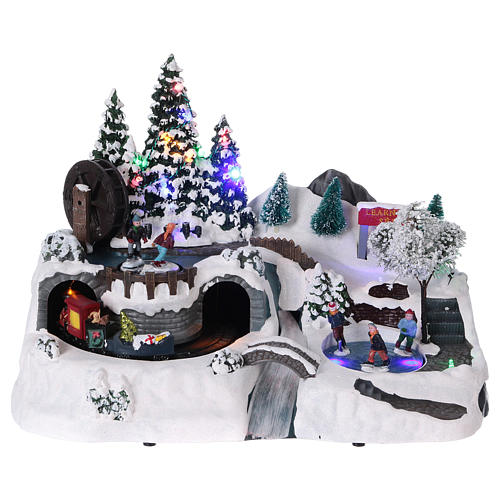 Christmas village with LED lights, moving ice-skaters and train 25x35x20 cm 1
