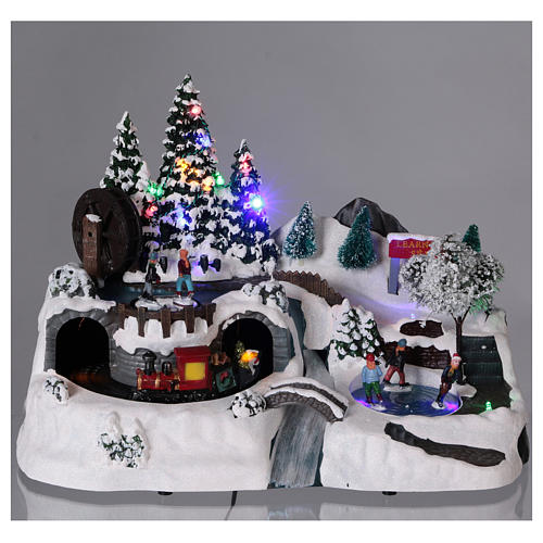 Christmas village with LED lights, moving ice-skaters and train 25x35x20 cm 2