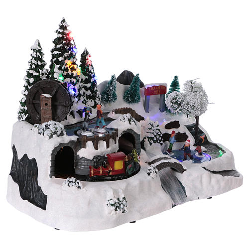 Christmas village with LED lights, moving ice-skaters and train 25x35x20 cm 4
