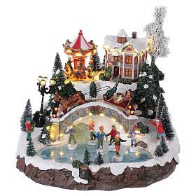 Weihnachtsdorf, mit Beleuchtung, Musik und beweglichen Eisläufern und kleinem Karussell, 30x35x35 cm, Netzanschluss s1