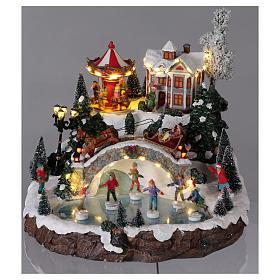 Weihnachtsdorf, mit Beleuchtung, Musik und beweglichen Eisläufern und kleinem Karussell, 30x35x35 cm, Netzanschluss s2