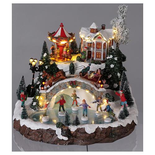 Weihnachtsdorf, mit Beleuchtung, Musik und beweglichen Eisläufern und kleinem Karussell, 30x35x35 cm, Netzanschluss 2
