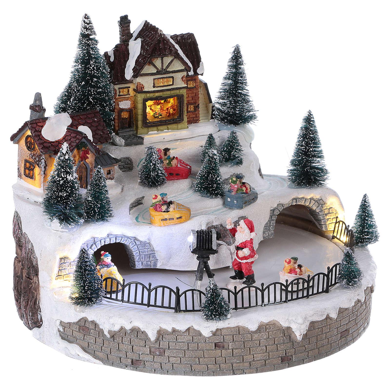 Pueblo navideño Papá Noel luces movimiento música 20x25x25 cm corriente 3