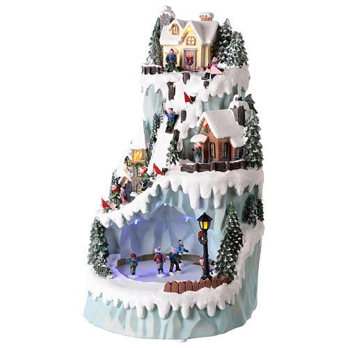 Villaggio natalizio in resina 43x24 cm con pista di pattinaggio in movimento 3