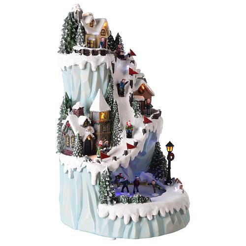 Villaggio natalizio in resina 43x24 cm con pista di pattinaggio in movimento 4