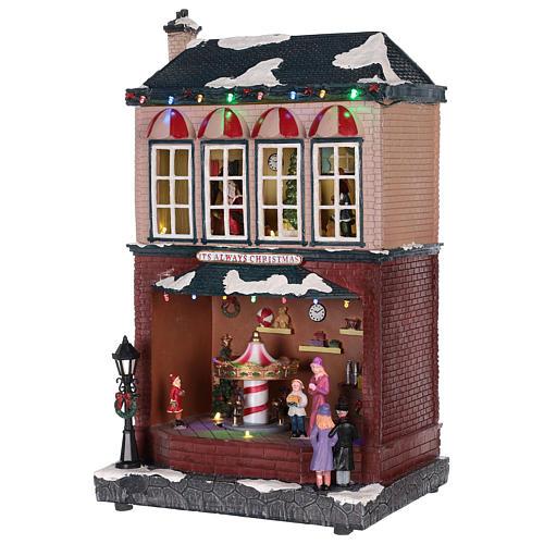 Casa de Navidad con tiovivo y Papá Noel 45x25x20 cm 9