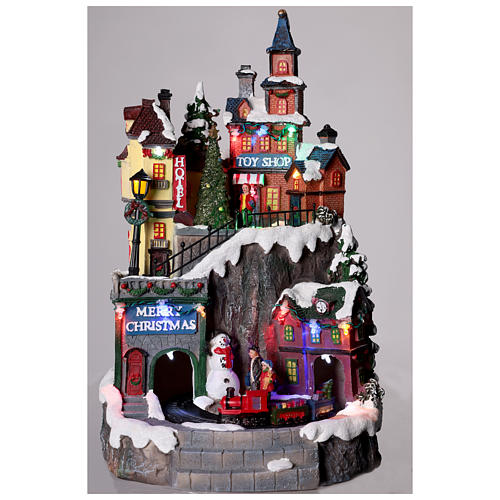 Pueblo navideño con tiendas movimiento luz música 35x20x20 2