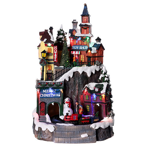 Village de Noël avec magasins mouvement lumière musique 35x20x20 cm 1