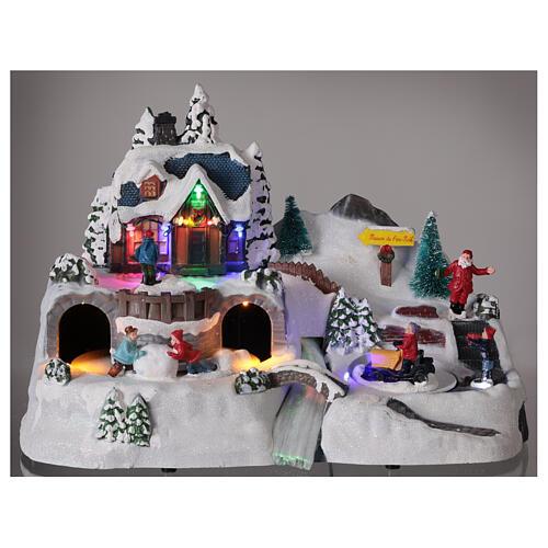 Aldeia de Natal nevada com crianças brincand na neve, luzes LED e música, 23,5x37,5x21,5 cm 8