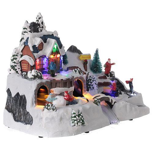 Aldeia de Natal nevada com crianças brincand na neve, luzes LED e música, 23,5x37,5x21,5 cm 10