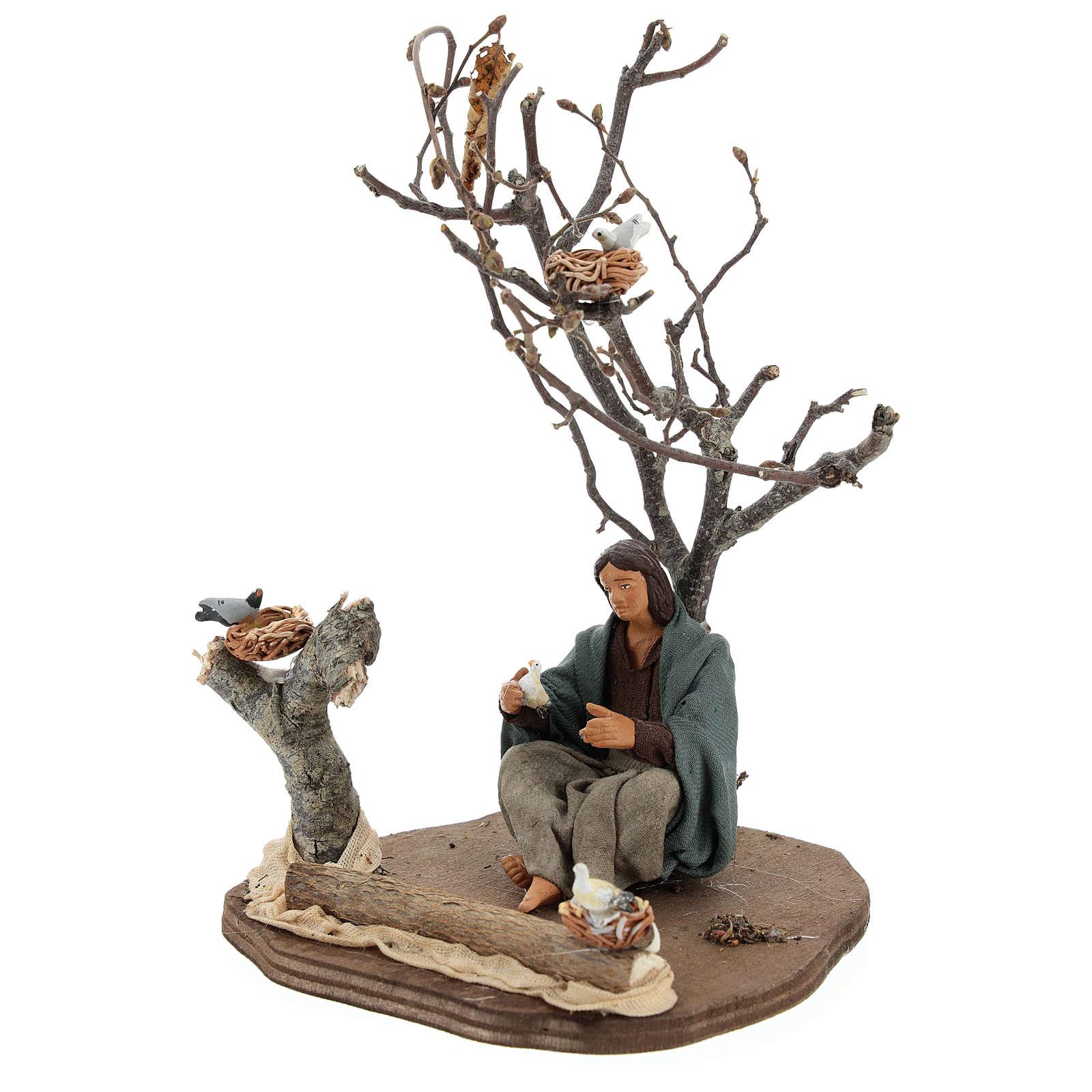 Donna seduta sotto l'albero con uccellini presepi 14 cm 4