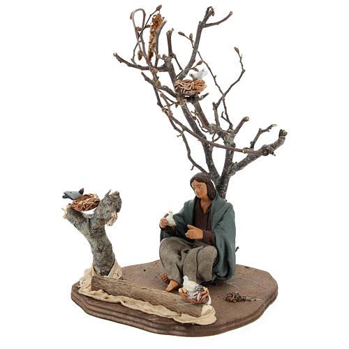 Donna seduta sotto l'albero con uccellini presepi 14 cm 3