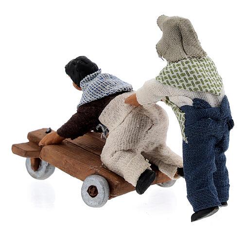 Duas crianças jogando com carrinho cena para presépio napolitano com figuras de altura média 10 cm 6